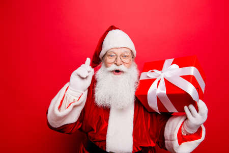 Ho ho! Holly jolly x mas! Noel magic! Funny kind astonished saint nicholas in traditional head wear is presenting a wrapped gift with white tape bow with forefinger up, isolated on red background Stock Photo