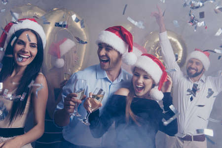 Entertain and night life mode. Group of jet set in luxury outfits, shirts, x mas headwear, rich, wealth, amazed, laughing, cheerful, at the club at new year. Many shining glitters explosion blast