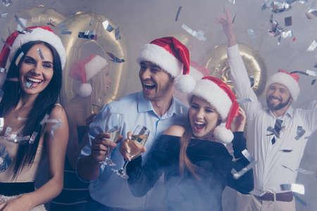 Unterhaltungs- und Nachtmodus. Gruppe des Jet in Luxus-Outfits, Hemden, X Mas Headwear, Reichtum, Reichtum, überrascht, lachend, fröhlich, im Club am neuen Jahr. Viele glänzende Glitzerexplosion Standard-Bild - 87790907