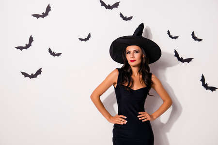 Let`s begin the creepy feast! Hot slim lady magician, in dark outfit, with arms on waist, in cap, with bright red lips, charming and elegant, stands on white wall background with small vampires