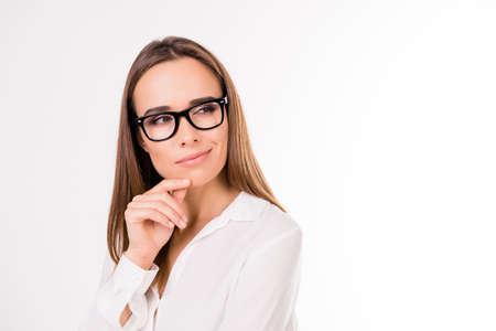 Close up portrait d'un modèle féminin aux cheveux bruns, inspirant, délicat et mignon dans des montures de lunettes noires cherche un espace vide pour la publicité, touchant doucement son menton avec ses doigts
