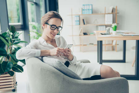 Comfort e luogo accogliente. Giovane donna carina in occhiali neri alla moda sta navigando sul suo telefono, seduto sulla poltrona. Lei è in completo formale, sorridente, seduta in un'atmosfera rilassante in ufficio Archivio Fotografico