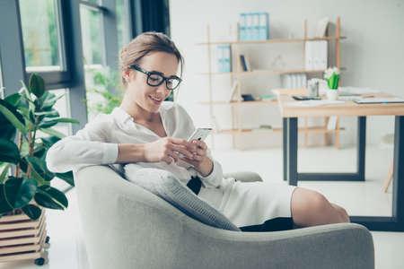 Confort y acogedor lugar. La señora linda joven en gafas de moda negras está hojeando en su teléfono, sentándose en la butaca. Ella está en traje formal, sonriendo, sentada en un ambiente relajado en la oficina Foto de archivo