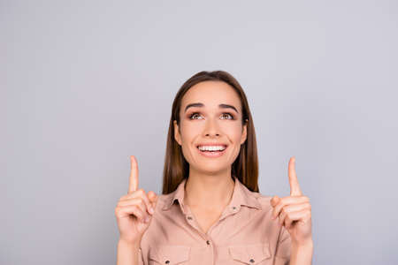 beaming: Look up! Close up portrait of beautiful smiling young business lady in a beige formal shirt, standing on the pure background, pointing at copyspace above with her fingers