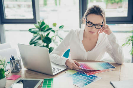 Successful attractive business lady designer is sitting at office, in formal wear, fashionable spectacles, such a cute smart professional, thinking, creating, imagining, generating new ideas, projects