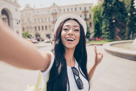 Cute lady with bronze skin and long dark hair, in cap is making a selfie shot while outside in town. She has a beaming smile, in white top, gestires peace sign, carefree and chilling mode
