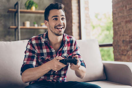 Close up of attractive hipster with bristle and toothy grin, holding joy stick and playing videogames on tv at vacation, sits at home on the cozy couch, successful, he is winning at crazy car race