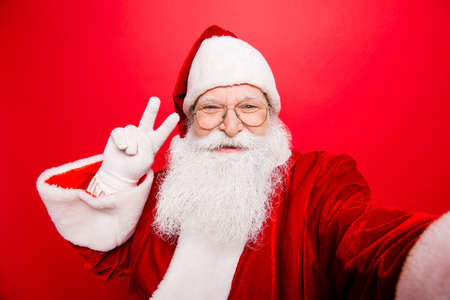 Taking holly jolly x mas festive memories. Funny Saint Nicholas photographer in red traditional outfit, head wear is showing peace gesture and makes shot on camera, isolated on red background Stock Photo