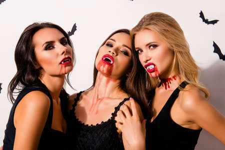 Elegant, playful, diabolic beauty of death. Gorgeous satanic bad withes, zombies, in fashionable dark dresses, shows cuspids, bonding on white background with bloody mouthes, ropping blood