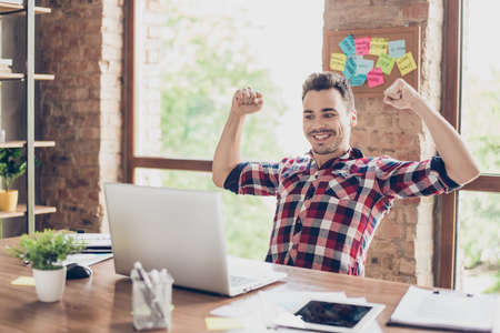 Yes! I did it! A dream of the young hipster freelancer entrepreneur came true. He is very excited, amazed, shocked, wearing smart casual, celebrating in the office Stock Photo
