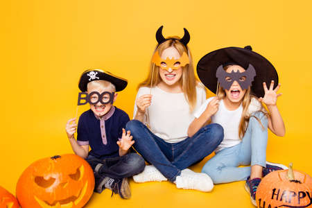 Close up portrait of mom with two small monsters, hiding behind eyemasks, with frightening gestures, sitting on the floor with crossed legs, handmade cutted pumpkin near, isolated on background