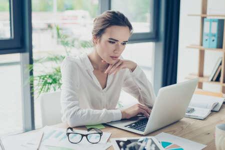 Gros plan portrait d'économiste sérieux jeune femme d'affaires en vêtements de cérémonie, assis sur son lieu de travail et concentré, en face de l'ordinateur portable, élégant, réussi, réfléchir, sérieux Banque d'images