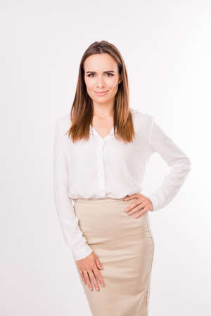 Attractive brown haired model in formal nice outfit, posing, touching her hip and waist, on pure snow white background, looking gorgeous. Work dress code, feminist concept Stock Photo