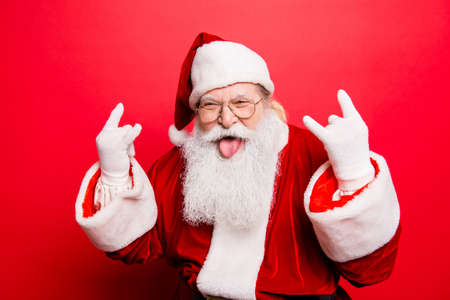It's party time! Holly jolly swag x mas and noel!  Cool funny playful naughty grandfather with sticking tongue, comic grimace, fooling around isolated on red background, shows rock gesture 免版税图像
