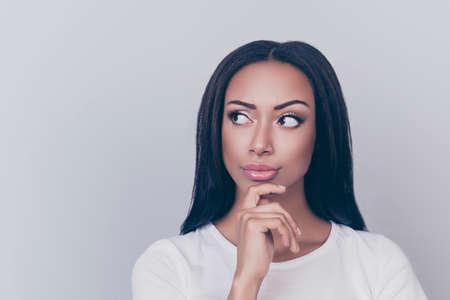 Schließen Sie herauf das Porträt des träumerischen Afro, der weg schaut und Kinn mit ihrem Arm berühren, ihre Gedanken sind weit entfernt und tragen die weiße zufällige Ausstattung, lokalisiert auf grauem Hintergrund, hat schönes dunkles Haar, Tageslicht bilden Standard-Bild