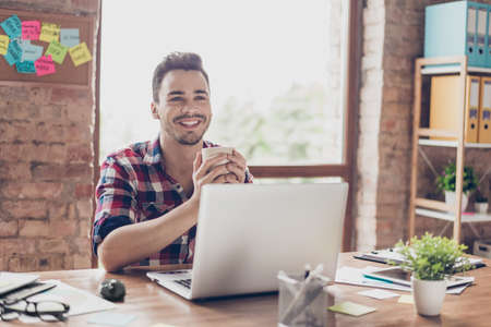 Low angle shot of successful happy brunet student, sitting with cup of tea, smiling, in front of computer, in casual checkered wear, at his work station in modern light office