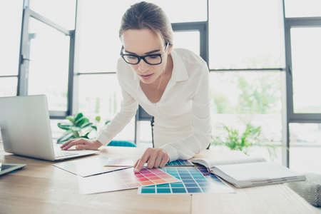 Creative occupation, making decision. Close up of female architect, in black trendy eyewear, whire formal outfit, choosing the colors for new project, looking at the pantone and pointing with finger