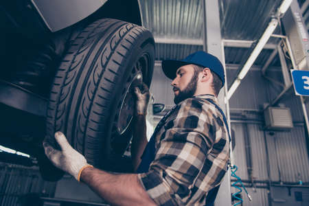 Low angle side profile shot of expert specialist technician changes tires, tyres of lifted up car, at auto workshop, wears checkered shirt, uniform costume, hat headwear