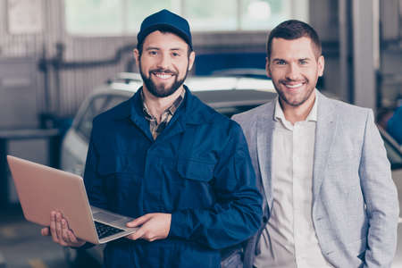 Two partners attractive guys, cheerful specialist repairman in blue costume, hat, holds his modern device, businessman in formal classy wear, blurred silver car behind. Vehicle breakdown, check