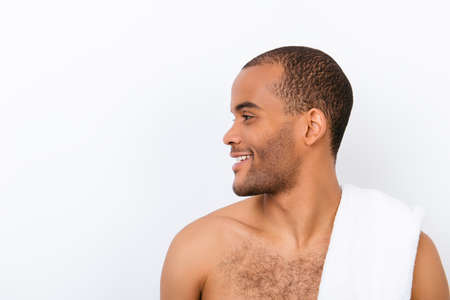 Hygiene, vitality, beauty, men life concept. Side profile view of afro young nude guy with white towel on his shoulder, isolated on pure background