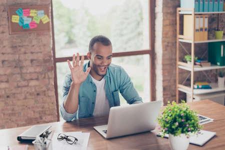 Il giovane tipo afroamericano allegro sta ondeggiando a porte chiuse mentre ha video chiamata che si siede al suo posto di lavoro in abbigliamento casual a casa