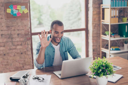 Young cheerful afro american guy is waving in camera while having video call sitting at his work station in casual clothes at home Banque d'images