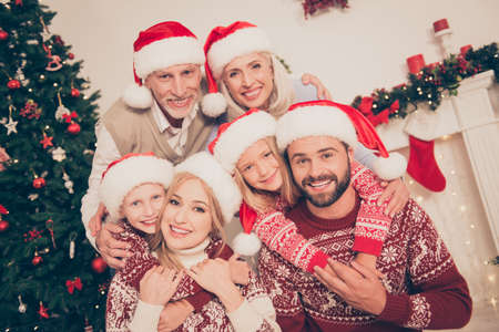 Six beautiful caucasian relatives embrace, married couples, excited siblings, grandad, granny, in knitted cute traditional x mas costumes,  pine firtree, home interior, stockings