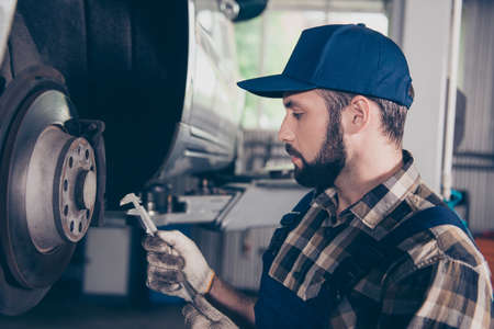 Brunet bearded engineer in checkered shirt, hat head wear is going to use a torque wrench socket and extension on the lug nuts of a car wheel. Check for safe travel, tuning, upgrading