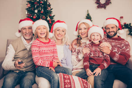 Group of cheerful relatives embrace bonding on couch, married couples, excited siblings, grandad, granny, in knitted cute traditional x mas costumes, pine firtree, home, movie, laugh