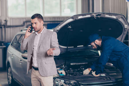 Attractive serious busy owner of a car, which gets appraising of damage by bearded expert specialist at auto workshop, is in classy formal outfit, having important call about his business