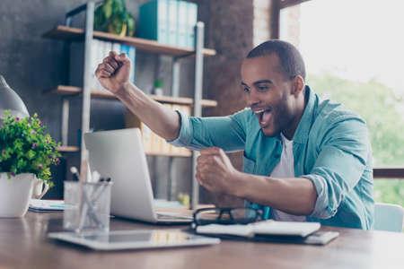 若いアフロ アメリカ起業家の夢が叶いました。彼は非常に興奮して着てスマート カジュアル、オフィスで祝う 写真素材