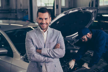 Close up portrait of excited attractive owner of a car, which gets appraising of damage by bearded expert specialist at auto workshop, is busy person in classy formal outfit, satisfied of service