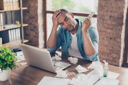 Young ill afro student is holding his forehead, having high temperature, at work place in modern office, a lot of paper  napkins on desktop, pills in his arm Stock Photo