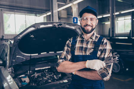 Attractive caucasian brunet bearded expert mechanic standing with metal mechanical keys in arm, in special safety outfit uniform, checkered shirt, hat head wear, open hood of vehicle