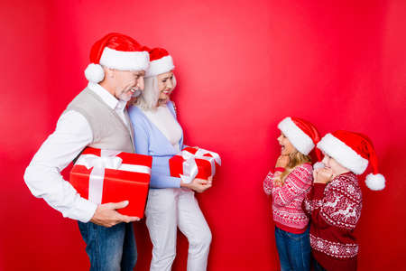 granny and grandad: Four relatives: married senior couple of grandad and granny, in knitted cute traditional x mas outfits prepard surprises for cheerful siblings full of emotions, isolated on the red background Stock Photo