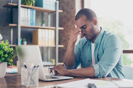 Stressed tired mulatto freelancer is having headache and thinking how to finish his work. He is in a casual smart, sitting and suffering at his home office, holding the nose bridge, massaging it