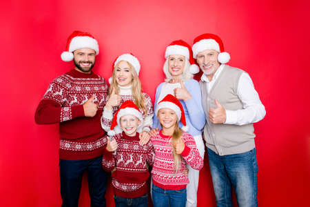 granny and grandad: We like holy magic x mas time! Six relatives bonding isolated on the red background, married couple, excited siblings, grandad, granny, in knitted cute traditional costumes, jeans, embracing Stock Photo