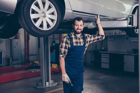 Attractive successful caucasian cheerful excited confident bearded brunet craftsman, handyman in special blue outfit, resting after upgrading transportation, standing underneath, smiling at camera