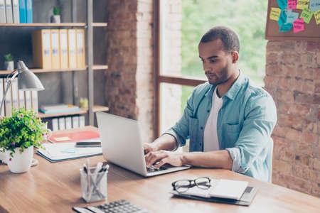 고 숙고 젊은 아프리카 잘 생긴 남자의 닫습니다. 그는 현명한 캐주얼 입고, 직장에 앉아 노트북 화면을보고 데이터를 입력합니다.