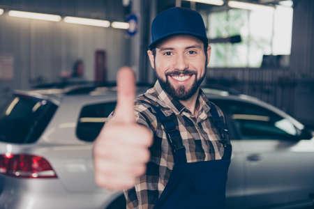 Engineering, industrie, mechanica, beroep, technologie. Sluit omhoog portret van aantrekkelijke kerel op het werkwinkel die thumbup gebaar tonen en bij camera, in speciale uitrusting, vage mening oh zijn wapen glimlachen Stockfoto