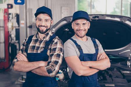 Aantrekkelijke vrolijke experts op de werkplaats, staand in een speciaal blauw veiligheidsuitrusting uniform, geruit overhemd, t-shirt, hoed hoofd slijtage, onscherpe achtergrond van de ingang van het voertuig, garage werkstation