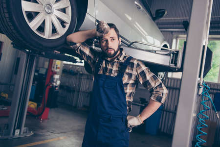 Dreamy attractive pensive ponder caucasian bearded brunet craftsman, handyman in special blue outfit, resting after upgrading transportation, standing leaning to it, looking far Stock Photo