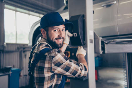 Closeup of cheerful brunet bearded expert in shirt and uniform, hat headwear, pressing the arm lever, car is lifted up, garage interior, work place, station. Engine, motor, transmission check concept