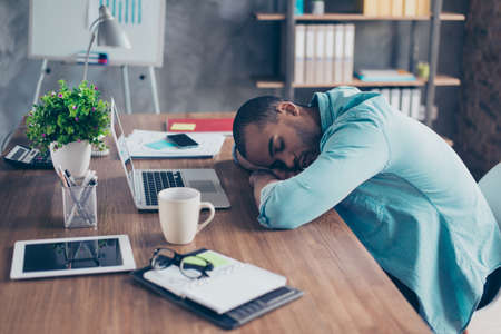 Sweet dreams in the work station. Sleepy tired freelancer is snoozing at his work place, coffee cup and office stuff near on desk top Stock Photo