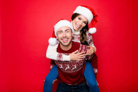 beaming: Cute excited partners with beaming smiles in knitted traditional clothing, head wear, guy holds hugs, piggy backing his lady with braid brunette hair.  December, winter, happiness x mas time!