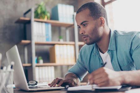クローズ アップのアフリカのハンサムな若者を熟考します。彼はカジュアル スマートを着て職場で座っている、ノート パソコンの画面を見て、そ