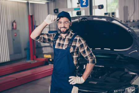 Attractive caucasian expert assistant at mechanical work shop, standing, fixing headwear, in special safety outfit uniform, checkered shirt, open hood of vehicle. Upgrading of auto