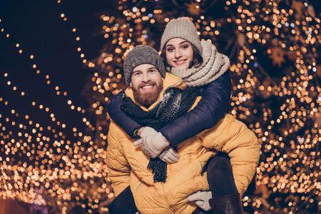 ハンサムな赤ひげを生やした男は冬の暖かい服を着て、彼のかわいい恋人をバックアップする貯金箱ヘッドの磨耗、それらの背後に x マスの輝き、
