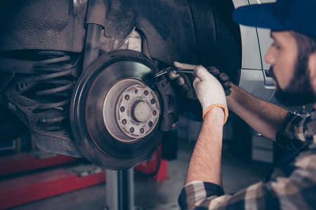 측면 프로필 전문 기술자 변경 타이어, 타이어 또는 브레이크 패드 자동 워크샵에서 들어 올려 최대 자동차의 닫기 최대 최대 바둑판 무늬 셔츠, 유니