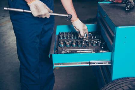 Geernteter Schuss des Ingenieurs, halten Rollenkupplungsschlüssel, setzen oder nehmen schmutzige Handschuhe auf Regal. Schraubenschlüssel und Sechskantadapter, Fitting, Hahn, Kappe, Chrom, Stahl, Rohr, Reihe von Optionen Standard-Bild - 88146284